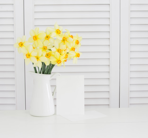 Primer de la flor amarilla del narciso en el florero sobre los obturadores blancos. decoración de estilo provenzal limpio