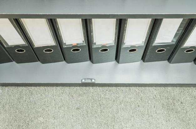 Primer grupo de archivos de documentos en archivador sobre fondo de alfombra gris