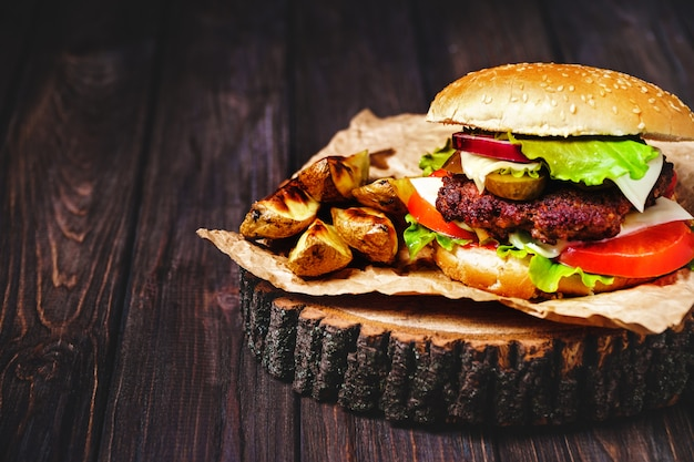 Primer de las hamburguesas caseras de la carne de vaca con lechuga y mayonesa servidas en pequeña tabla de cortar de madera.
