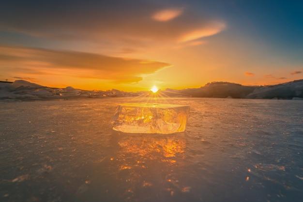 Primer del hielo de fractura natural en el agua congelada en la puesta del sol en el lago baikal, siberia, rusia.