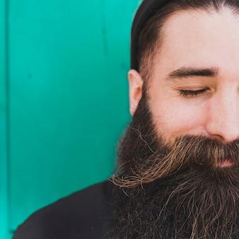El primer del hombre barbudo con el ojo se cerró contra el contexto verde