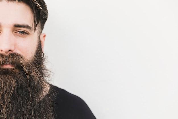 Primer del hombre joven barbudo que mira la cámara contra el contexto blanco