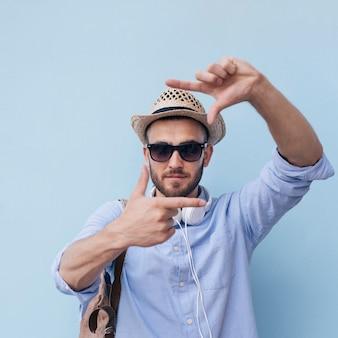 Primer del hombre joven elegante que hace el marco de la mano contra la pared azul