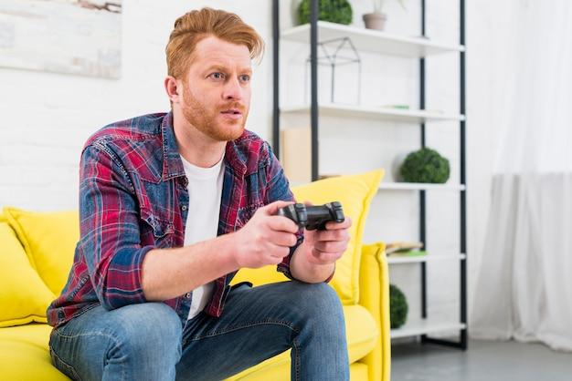 Primer del hombre joven que se sienta en el sofá amarillo que juega al videojuego con la palanca de mando en la sala de estar
