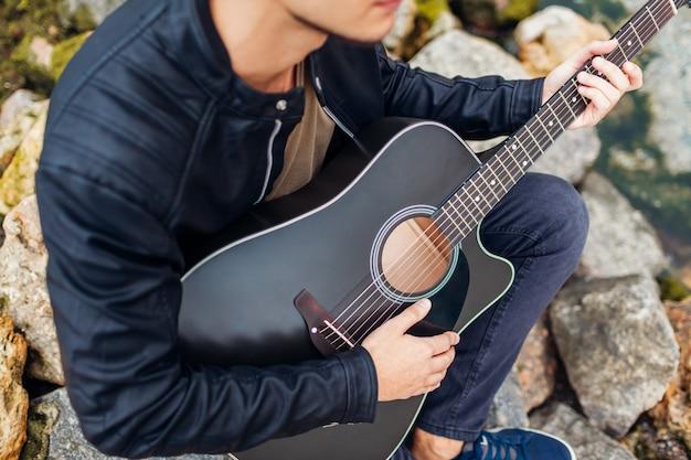Primer del hombre joven que toca la guitarra acústica en la playa rodeada con las rocas en día lluvioso