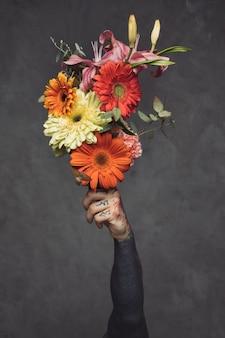 Primer del hombre joven tatuado que sostiene el ramo floral disponible contra la pared gris