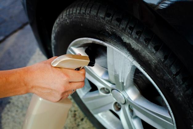 Primer hombre mano rociando una rueda de coche