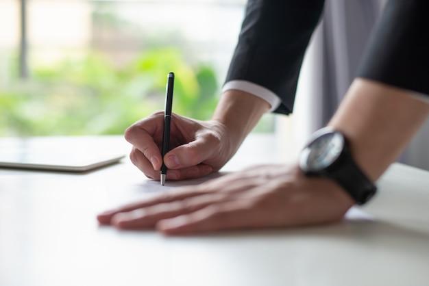 Primer del hombre de negocios que escribe en la hoja de papel en el escritorio