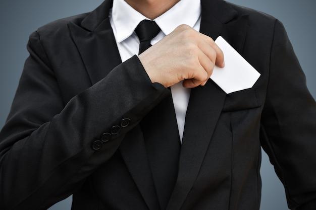 Primer del hombre de negocios que saca el trozo de papel blanco del bolsillo en traje negro. idea para tarjeta de crédito comercial o tarjeta de visita.