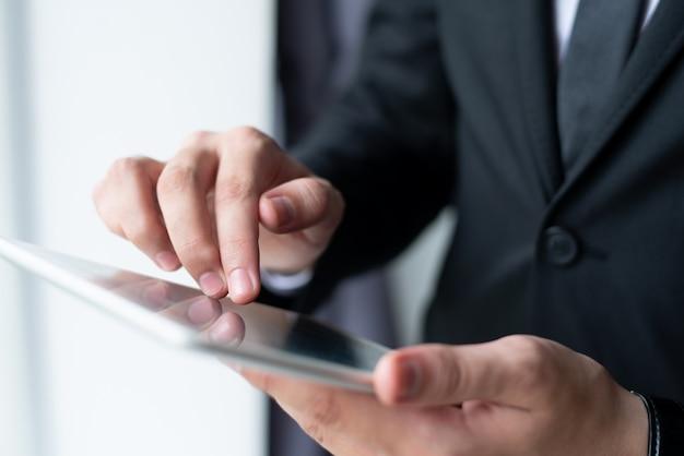 Primer del hombre de negocios que sostiene y que usa la tableta