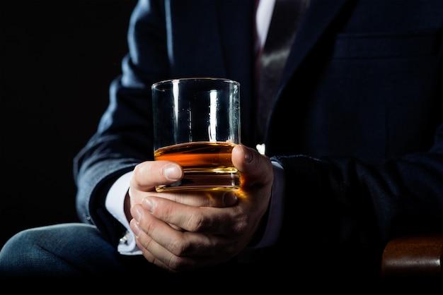El primer del hombre de negocios serio que sostiene el whisky ilustra concepto de privilegio ejecutivo.