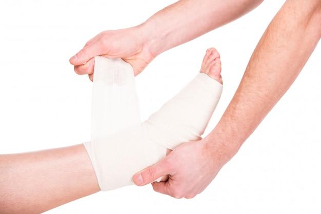 Primer hombre está poniendo vendaje en los pies heridos.