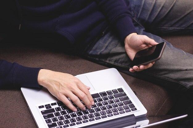 Primer del hombre que se relaja usando smartphone y el ordenador portátil que se sientan en el sofá.