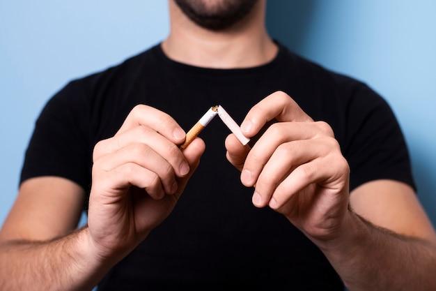 Primer hombre rompiendo cigarrillo