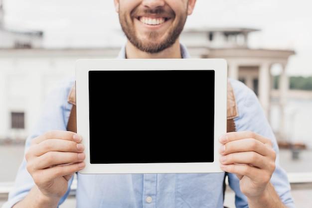 Primer del hombre sonriente que muestra la tableta digital