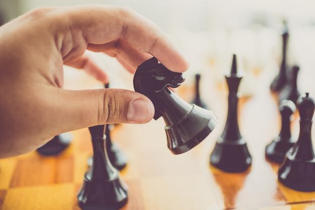 Primer hombre tonificado haciendo movimiento con caballo negro en el juego de ajedrez
