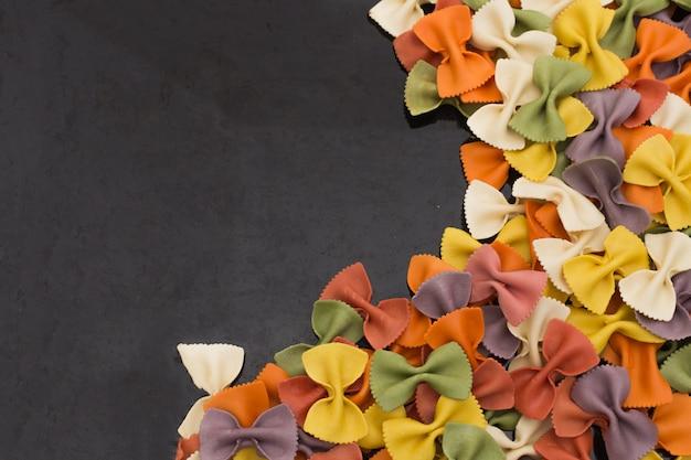 Primer italiano de las pastas farfalle multicoloras crudas en fondo negro con el espacio de la copia.