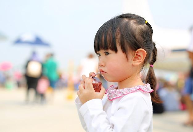 Primer de la leche de consumo de la niña con la paja. retrato al aire libre.