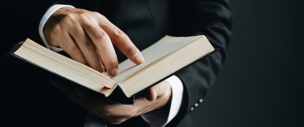 Primer de la lectura del dedo del hombre que señala el texto en libro.
