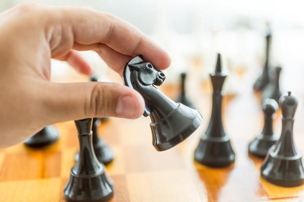 Primer macho mano sujetando la pieza de ajedrez caballo negro