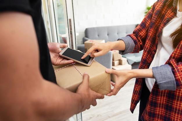 El primer de la mano del cliente confirma recibir el paquete postal en línea en el móvil.