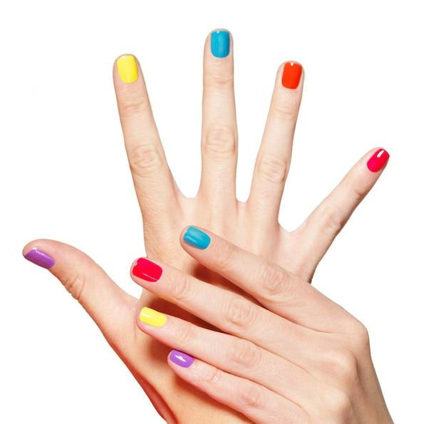 Primer mano femenina con uñas multicolores sobre blanco.