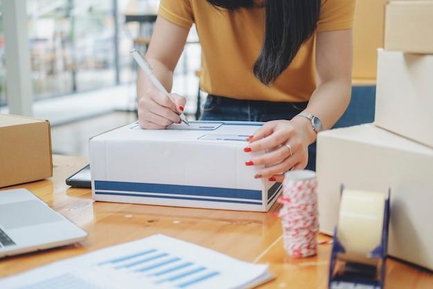 Primer mano de la mujer joven escribiendo la dirección en la caja del paquete para la orden de entrega al cliente, envío y logística, comerciante en línea y vendedor, propietario de negocio o pyme, compras en línea.