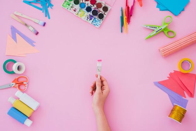 Primer de la mano de la mujer que sostiene el pincel con la paleta de colores del agua; cepillo de pintura; papel; tijera sobre fondo rosa