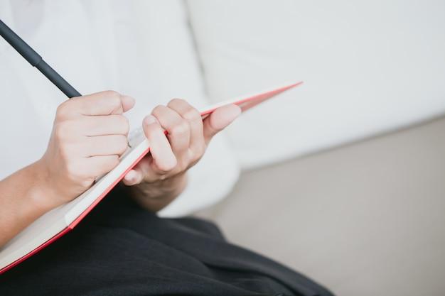 Primer mano de las mujeres de trabajo escribiendo nota de nota con copyspace