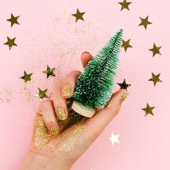 Primer mano que sostiene el árbol de navidad