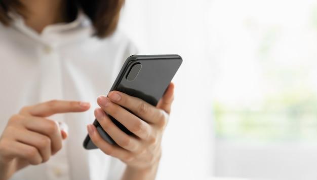 Primer de la mano que sostiene el dispositivo del smartphone y que escribe el mensaje de texto en social en línea.
