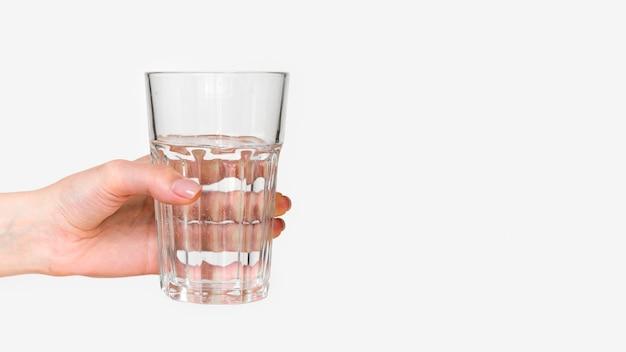 Primer mano que sostiene el vaso de agua