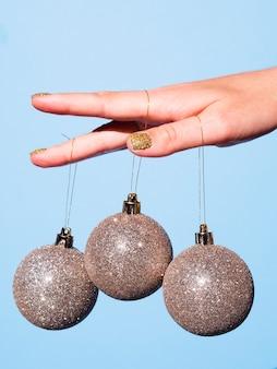 Primer mano sosteniendo bolas decorativas