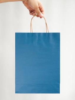 Primer mano sosteniendo una maqueta de bolsa azul