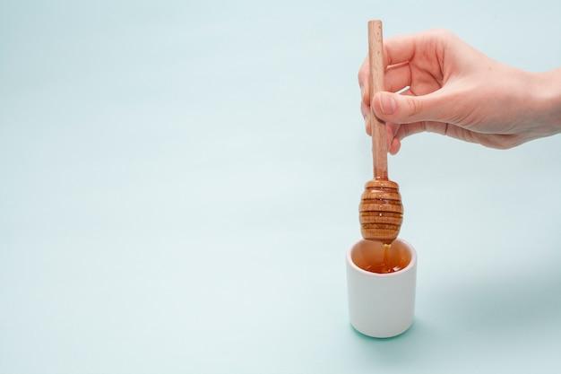 Primer mano sosteniendo palo de miel