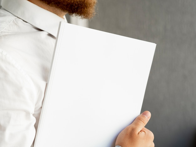 Primer mano sosteniendo una pila de maquetas de papel