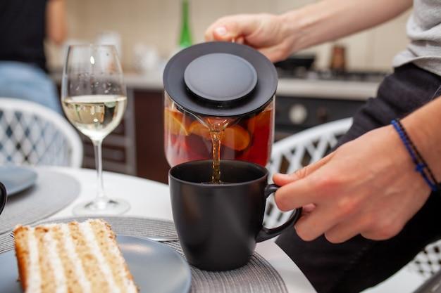 Primer de las manos masculinas que vierten té en una taza. al lado de la mesa hay una copa de vino y un trozo de tarta