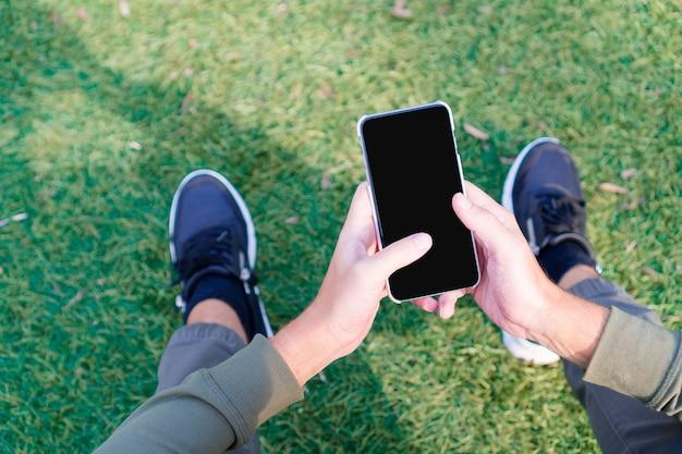 El primer de las manos masculinas está sosteniendo el teléfono móvil al aire libre en la calle. hombre con teléfono inteligente móvil.