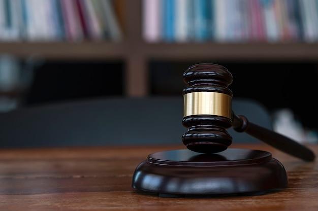 Primer martillo del juez sobre la mesa de madera en una habitación oscura con fondo borroso. concepto de ley.