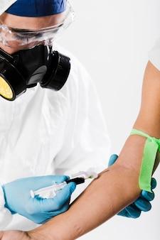 Primer médico tomando muestras de sangre de una persona enferma