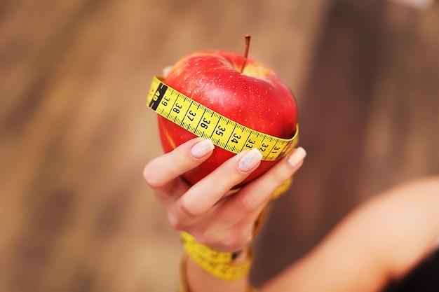 Primer en medir la manzana en manos caucásicas del `s de la mujer.