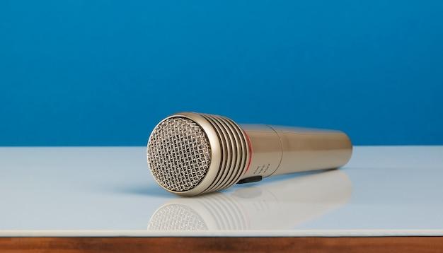 Primer micrófono sobre una mesa de espejo blanco