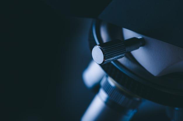 Primer del microscopio científico con la lente metálica en el laboratorio, equipo de laboratorio - microscopio óptico.