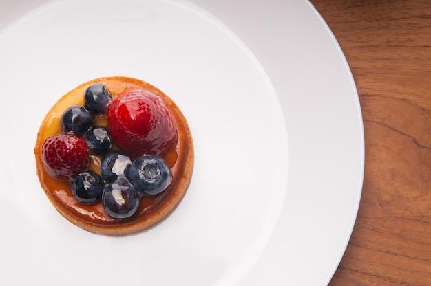 Primer de la mini tarta deliciosa con las bayas en la placa blanca