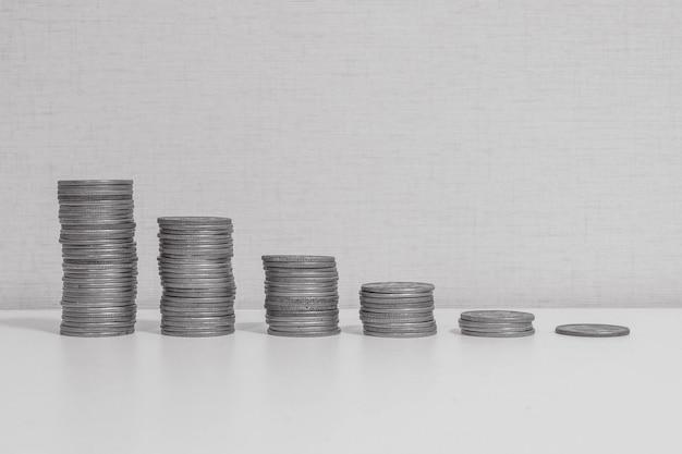 El primer montón de monedas comienza de alto a bajo en el escritorio de madera