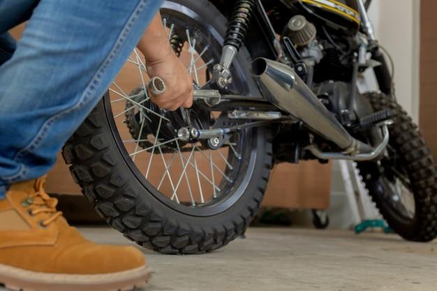 Primer de la motocicleta de la fijación de la mano del hombre joven, de la afición mecánica y del concepto de las reparaciones.