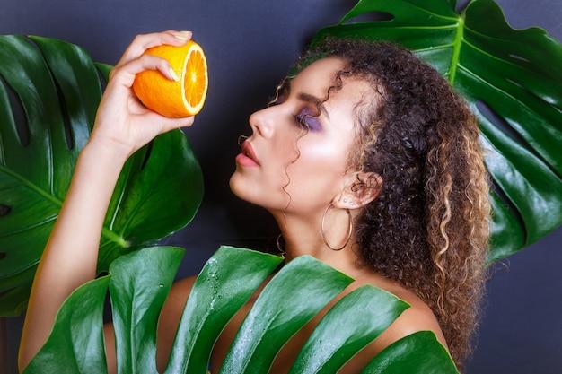 Primer de la muchacha hermosa que presenta en bosque tropical. retrato de hermosa mujer afroamericana con frutas tropicales