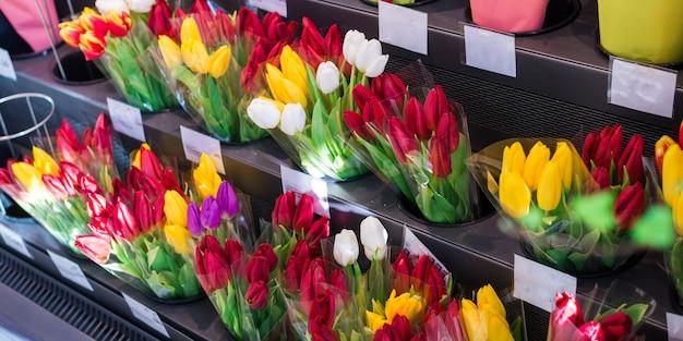 Primer de muchos ramos rosados, rojos, amarillos del tulipán en una floristería, un mercado o una tienda de flores.