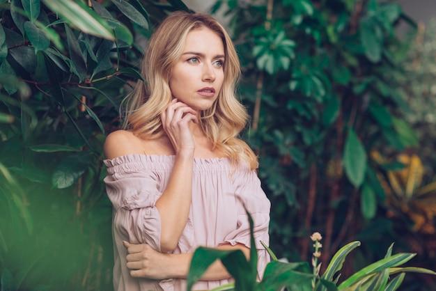 Primer de la mujer joven rubia pensativa que se coloca en el jardín que mira lejos