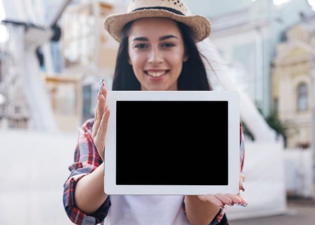 Primer de la mujer joven sonriente que muestra la tableta digital